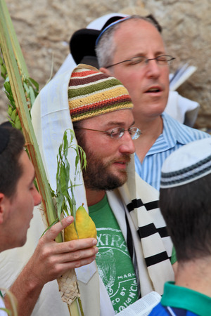 sukkoth festival: JERUSALEM, ISRAEL - SEPTEMBER 20, 2013: Young religious Jew in a knitted skullcap and talite with citrus-etrog praying in the morning of Sukkot