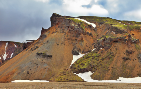 hollows: Rhyolite mountains. Colorful smooth mountains in the Icelandic reserve Landmannalaugar. In the hollows is last years snow