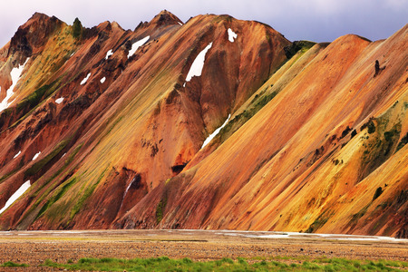 hollows: Smooth orange rhyolite mountains in Landmannalaugar nature reserve. In the hollows is last years snow Stock Photo
