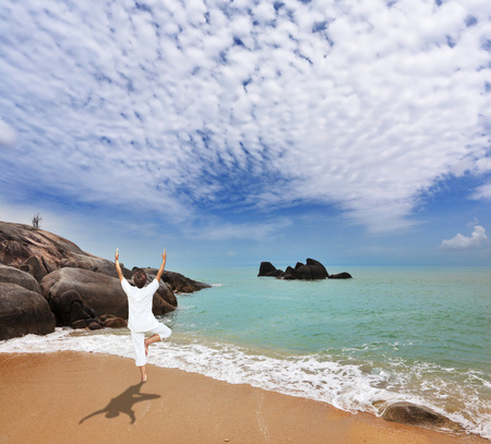 Thailand. Gorgeous beach on the Andaman Sea. Middle-aged woman dressed in white doing yoga.  Pose Tree, stand on one leg Фото со стока