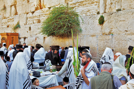 sukkoth: JERUSALEM, ISRAEL - SEPTEMBER 20, 2013: The Western Wall of the Temple in Jerusalem. Many religious Jews in traditional white robes tallit gathered for prayer. Morning Sukkot