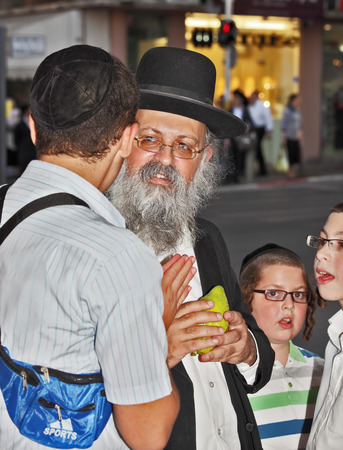 bene: BENE - BERAK, ISRAEL - SEPTEMBER 17, 2013:  The elderly man with gray-haired beard chooses a citrus.  Big market on the eve of Sukkot