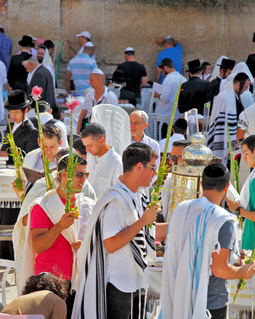 sukkoth festival: JERUSALEM, ISRAEL - SEPTEMBER 20, 2013:The Western Wall of the Temple in Jerusalem. Many religious Jews in traditional robes tallit gathered for prayer. Morning Sukkot Editorial