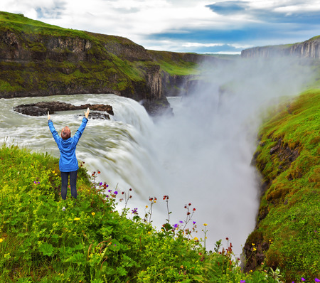 Powerful Gullfoss in Iceland. On the hillside woman thrilled looking at the boiling abyss photo