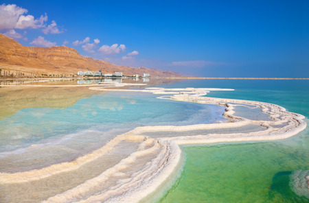 dead: Israeli coast of the Dead Sea. The path from salt picturesquely curls in salty water. Hotels are reflected in smooth water ashore