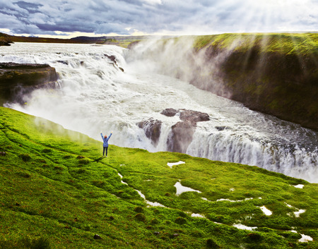 On the hillside woman thrilled looking at the boiling abyss. Powerful Gullfoss in Iceland. photo