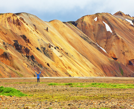 remained: Pink and orange Mountains National Park Landmannalaugar in Iceland. At the foot of the mountains is worth admiring woman -turist. Snow remained on the mountains last year.