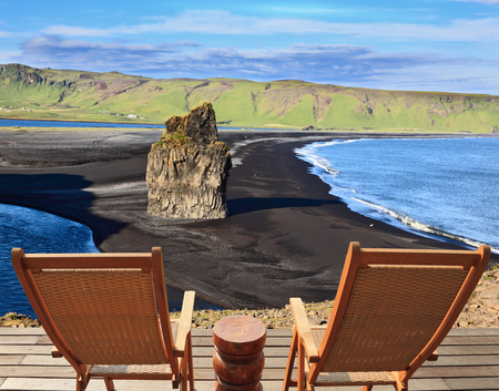 loungers: Rock in the sand. Cape Dirholaey in southern Iceland. On a coastal rock delivered comfortable wooden loungers