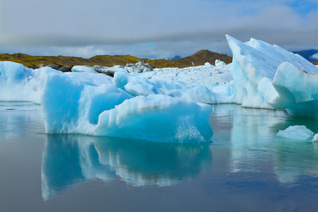 ice floes: The blue and emerald icebergs and ice floes floating in the gulf Jökulsárlóн in Iceland. Sunrise.