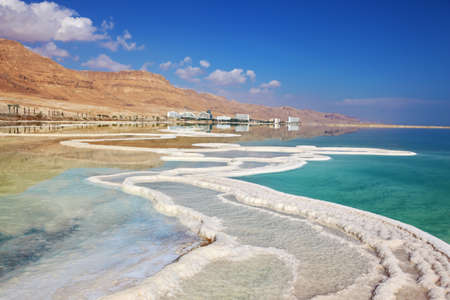 rock salt: Israeli coast of the Dead Sea. Path from the salt winds picturesquely in salt water. Hotels on the bank are reflected in smooth water Stock Photo