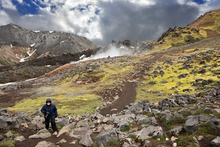 hollows: Rhyolite mountains smoldering underground heat. In the hollows lie unmelted snow patches from last year. Mature woman tourist wearing warm up the trail. Iceland in July