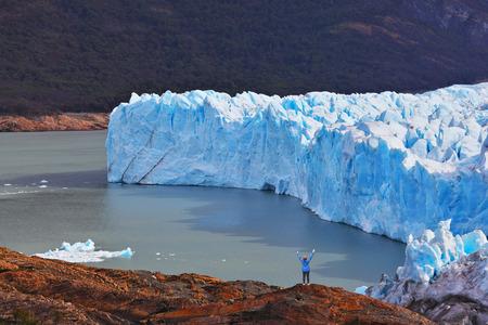 admire: The woman - tourist admire the white-blue icy splendor. Giant lake Perito Moreno glacier