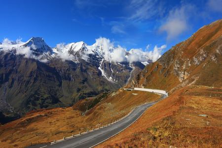 Austrian Alps. Excursion to the picturesque panoramic way Grossgloknershtrasse. Sunny day in early autumn. Tape highway winds between hillsides yellowed