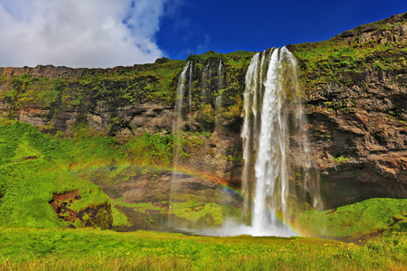waterfall with sky: Seljalandsfoss waterfall in Iceland. Sunny day in July. Large rainbow decorates a drop of water