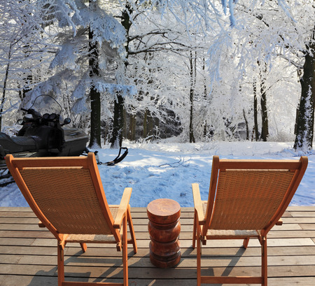 round chairs: Christmas in the forest. Trees covered with snow. Comfortable wooden chairs and a small round table invite tourists to relax and enjoy the winter wonderland Stock Photo