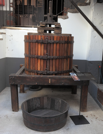 FUNCHAL, MADEIRA - OCTOBER 08, 2011: The museum - storage of expensive vintage wine Madeira. An ancient press for a grapes extraction