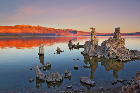calcareous: The magic of Mono Lake. Outliers -calcareous tufa formation on the smooth water of the lake. Orange sunset
