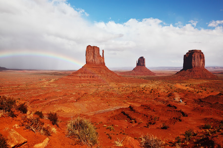 intersect: Red stone desert Navajo, USA. Isolated rocks - mitts intersect with the beautiful rainbow.