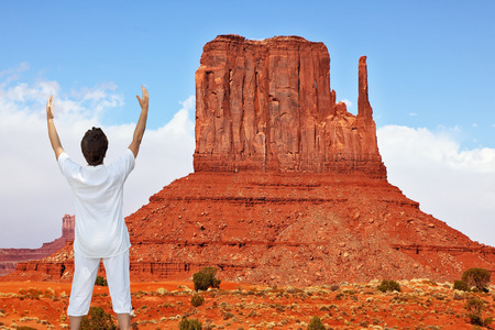 mitts: Woman in white performs asana Sun salutation. Navajo Reservation in the US. Red Desert and rocks - mitts sandstone
