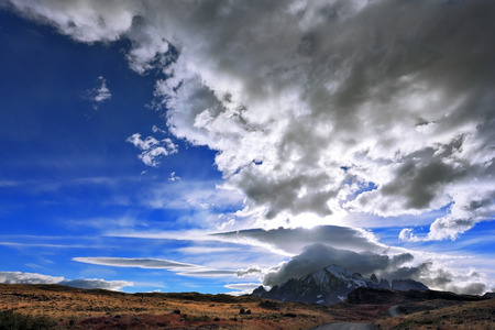 glisten: The Chile National Park Torres del Paine. Incredible shaped cloud formed by glaciers glisten in the sun. On the horizon are seen mountains with snow-capped peaks. Picture taken with a fisheye lens