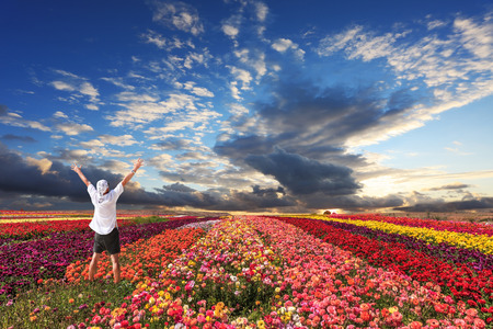 threw: Enthusiastic tourists threw up his hands. Cloudy and windy spring day. Bright festive red, pink and yellow  blooming field of buttercups