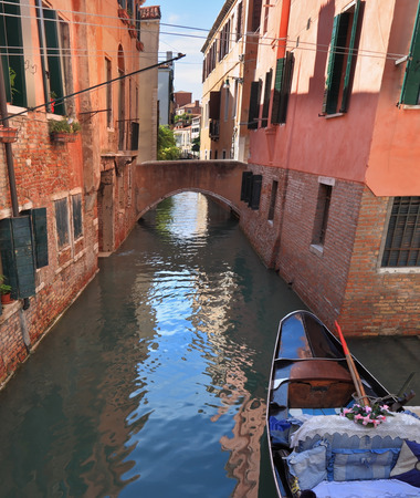 approached: Eternal fabulous Venice. The narrow street - channel brightly lit afternoon sun. Against the wall approached by gondola