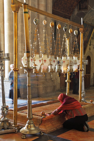 passionately: Temple of the Holy Sepulcher in Jerusalem. The oldest Christian sanctuary - Stone of Unction. The pilgrim in red clothes passionately prays under icon lamps.