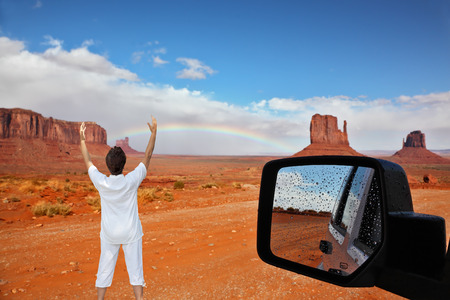 threw: Monument Valley. Arizona, USA. The unique red sandstone buttes are reflected in the car mirror. The woman -  tourist threw up her hands in delight Stock Photo