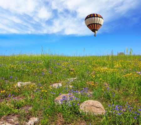 golan: In a clear sky flying big colorful balloon. Flowering Golan Heights in a beautiful sunny day