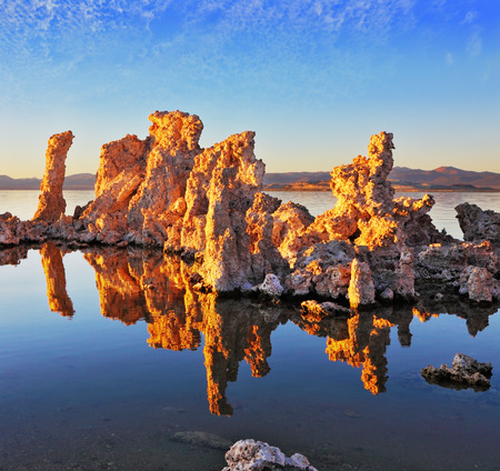 calcareous: Orange sunset. The magic of Mono Lake. Outliers - calcareous tufa formation  on the smooth water of the lake Stock Photo