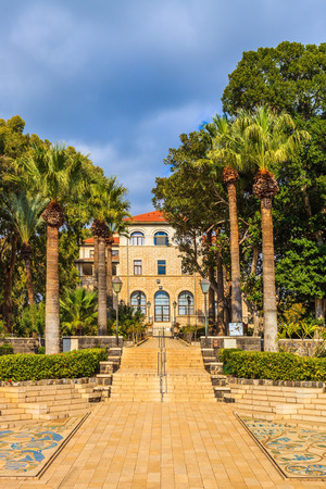 leading light: Roman Catholic Church of the Beatitudes. Stone path leading to the buildings of the monastery. Palm park gives light shade
