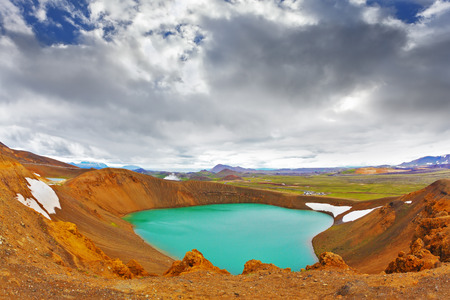 crater highlands: Summer in Iceland. Picturesque lake in the crater of an extinct volcano. Lake water bright green color. On the shores lie snowfields from last year Stock Photo