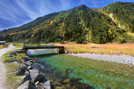 spanned: Starting famous Krimml waterfalls. Crystal clear water sparkles in the midday sun. Through the narrow creek wooden bridge spanned. Austrian Alps