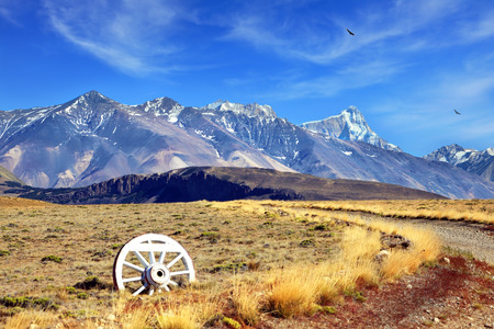 wagon: Road sign in the form of a wagon wheel. Gravel road in the desert. In the distance the snow-covered mountains. Argentine Patagonia, Perito Moreno National Park Stock Photo