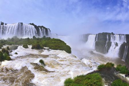 turbid: Raging and roaring water in the waterfalls of Iguazu. Turbid yellow-brown waves flow down. The Brazilian side