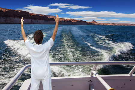 admiring: Artificial lake Powell on the Colorado River, USA. The lake is surrounded by picturesque beaches of the orange sandstone. Middle-aged woman in white at the stern of the ship admiring the beauty of nature Stock Photo