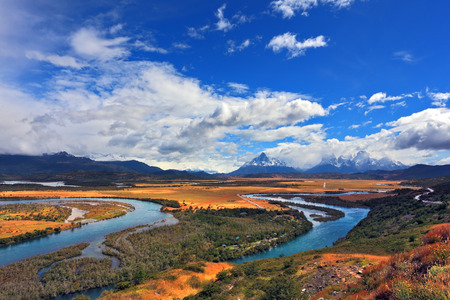 meandering: Meandering river bed of yellow autumn coast. Valley surrounded by snow-capped mountains. Glen Serrano Stock Photo
