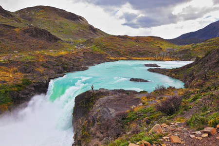 edge of cliff: Gorgeous National Park in Chilean Patagonia. Affluent bustling Salto Grande waterfall with emerald water. On the edge of the cliff stands tourist Stock Photo