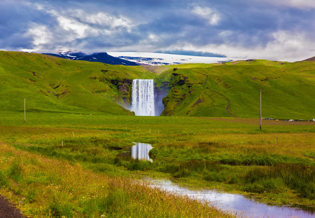 The huge deep falls Skogafoss are reflected in small stream. Grandiose reflection photo