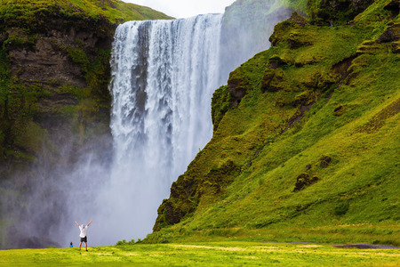 Grand waterfall Skogafoss in Iceland. Tourist in shirt and bandana threw up his hands with delight the beauty of nature 免版税图像