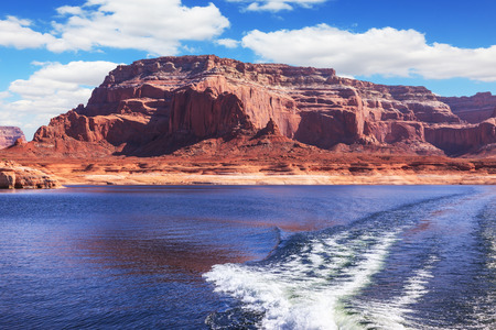 foamy: Foamy trace of motorboat crosses the emerald waters. Red sandstone hills surround the lake. Lake Powell on the Colorado River