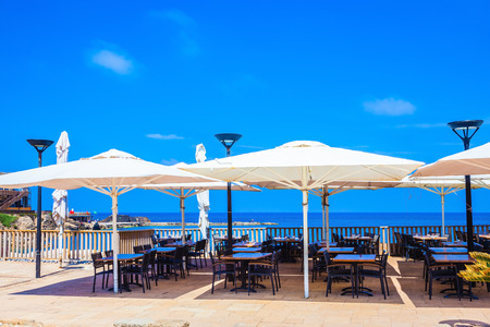 disclosed: Cozy cafe on the shore of warm sea. Above the tables are disclosed white tents