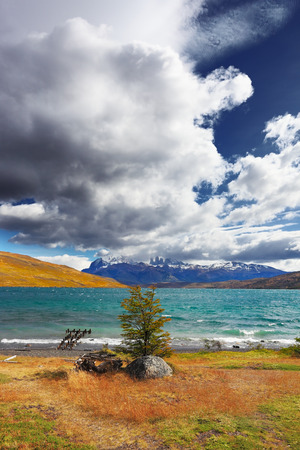gale: The gale on Lake Laguna Azul. A huge cloud covers the sky. In the distance the mountains with snow-capped