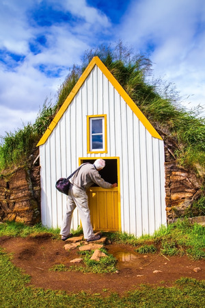 reconstituted: The village first settlers in Iceland. The reconstituted village - Pioneer Museum - Viking. Curious tourist with camera bag looks at the door house