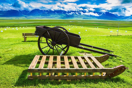 reconstituted: Old wooden sledge and two-wheeled cart on the lawn. The reconstituted village -  Museum Vikings in Iceland Stock Photo