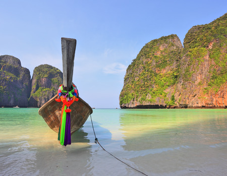 approached: Scenic green islands of Thailand coast. Emerald sea and fine white sand. On the beach approached by a native boat for tourists, decorated with a red silk scarf Stock Photo