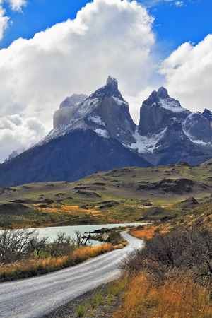 grandiose: Grandiose landscape in the Chilean Andes. The road between turned yellow hills goes to snow-covered black rocks. Patagonia