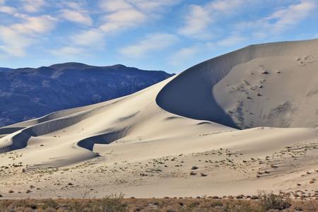 hollows: Eureka - a huge sand dune at sunrise. A thin ridge of dunes and deep shadows in the hollows. California, USA