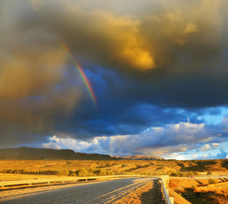 the pampas: Low swirling cloud and flat plain covered in orange sunset. Cloud crosses the rainbow. In the steppe runs a gravel road. Storm over the Pampas Stock Photo