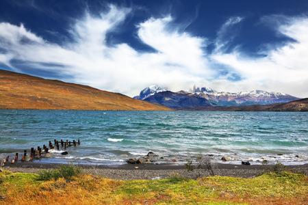 espumante: La tormenta en el lago. Las monta�as que rodean el lago, casi ocultas nubes volando. Muelle vierte espumosas olas Foto de archivo